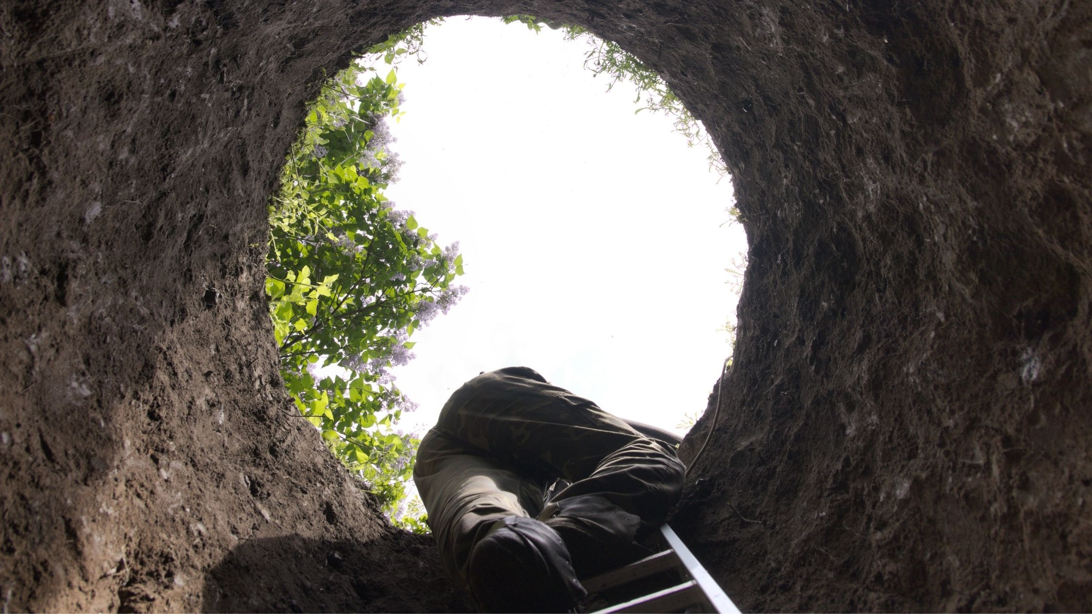 Person climbing out of a hole metaphor for climbing out of debt